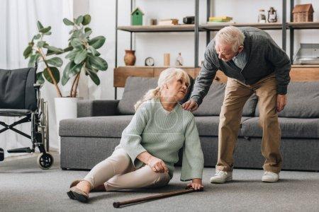 Photo pour Senior femme, assis sur le sol avec une douleur au genou près de soutien retira mari - image libre de droit