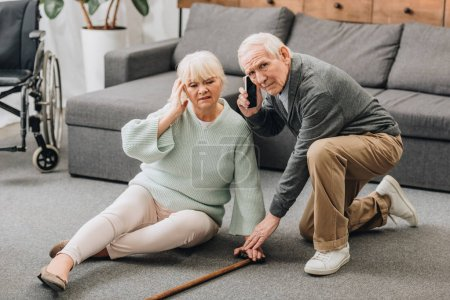 Foto de Senior mujer sentada en el piso mientras marido jubilado hablando en teléfono inteligente - Imagen libre de derechos