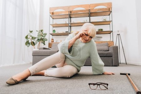 Photo for Retired woman with blonde hair sitting on floor in living room while having headache - Royalty Free Image