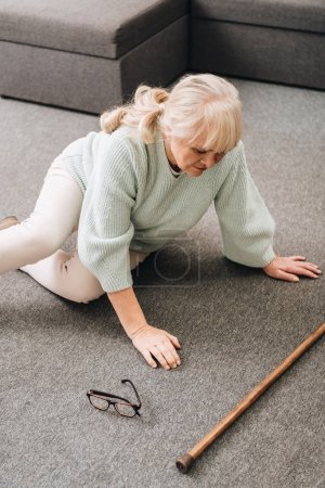 helpless senior woman with blonde hair sitting on floor at home