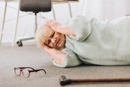 Foto de Mujer retirada indefensa tirado en piso en sala de estar teniendo dolor de cabeza - Imagen libre de derechos