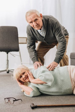 Photo for Old men helping wife who falled down on floor  and looking at camera - Royalty Free Image