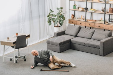 Photo for Old man falled down on floor of the room near walking stick - Royalty Free Image