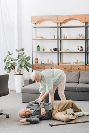 Photo pour Vieille femme aide son mari qui tombaient vers le bas sur le plancher - image libre de droit
