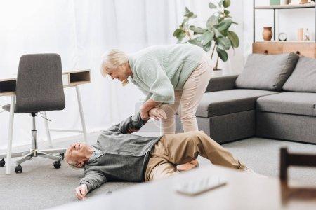 Photo pour Vieille femme aidant à son mari qui tombaient vers le bas sur le plancher - image libre de droit