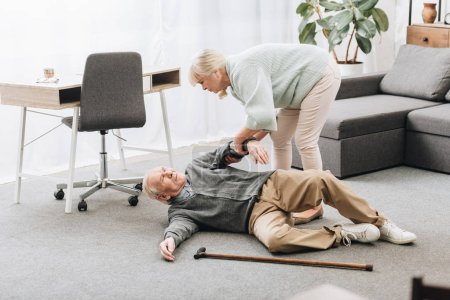 Old woman helping husband who falled down with hea...