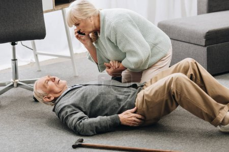 senior woman looking at husband who falled down with heart attack and dying