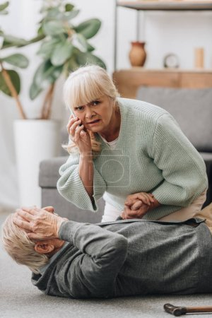 senior woman helping old man with walking stick and looking at camera