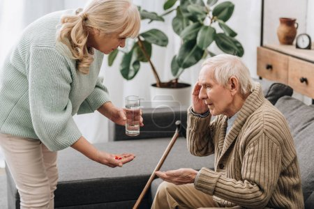 Photo for Senior woman giving pills to old man with walking stick - Royalty Free Image