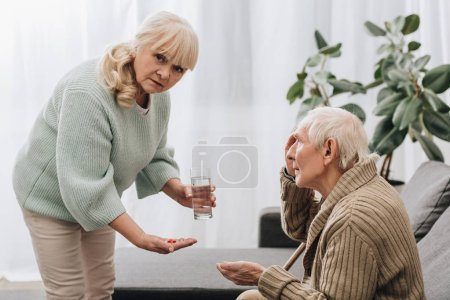 Photo for Senior woman giving pills and glass of water to old man and looking at camera - Royalty Free Image