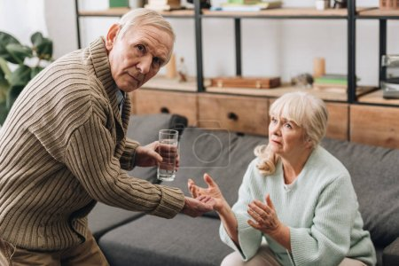 Photo for Senior man giving to old woman glass of water and pills while looking at camera - Royalty Free Image
