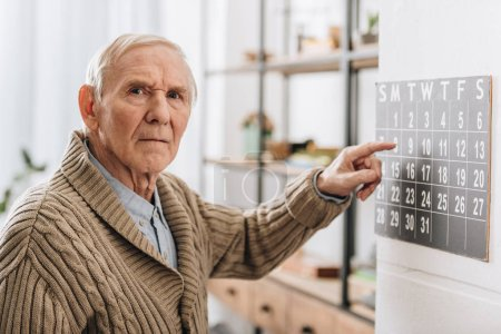Photo for Old man touching calendar looking at camera - Royalty Free Image