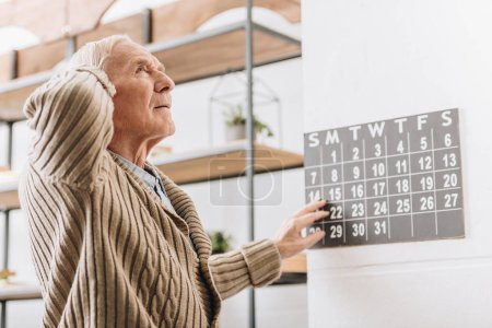 Photo for Senior man touching wall calendar and head - Royalty Free Image
