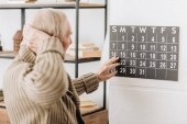 man with grey hair touching wall calendar and head