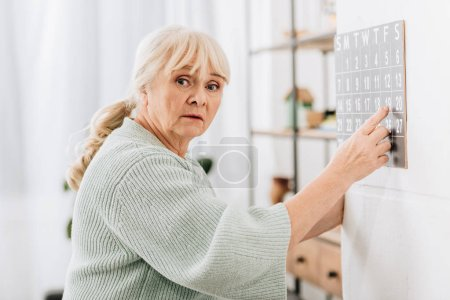 upset senior woman touching wall calendar and looking at camera