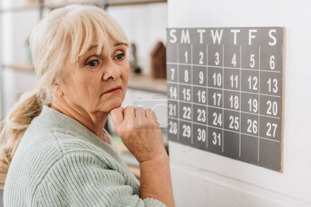 upset senior woman touching wall calendar and remembering dates