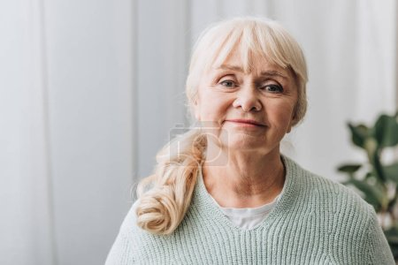 cheerful senior woman with blonde hair at home