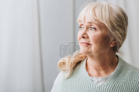 dreamy senior woman with blonde hair at home