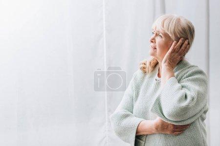 retired woman with blonde hair having headache