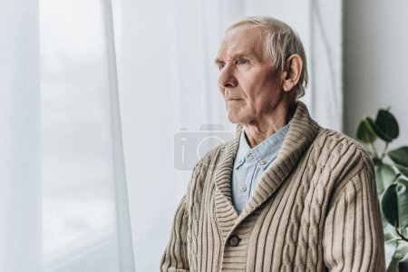 upset retired man with dementia disease standing at home