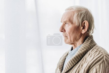 sad senior man with dementia disease at home