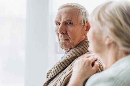 selective focus of senior husband standing with retired wife at home