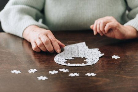 cropped view of senior woman playing with puzzles on table