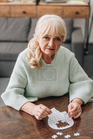 blonde senior woman playing with puzzles at home
