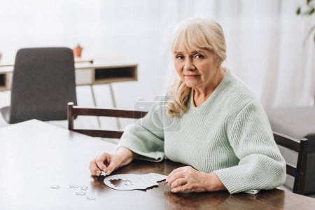 Photo for Blonde retired woman playing with puzzles at home - Royalty Free Image