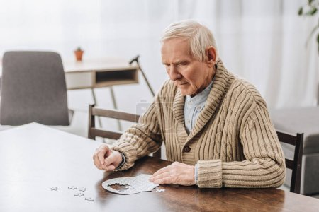 Photo for Pensioner with grey hair playing with puzzles at home - Royalty Free Image
