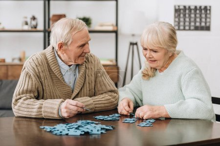 Photo for Happy retired couple playing with puzzles at home - Royalty Free Image