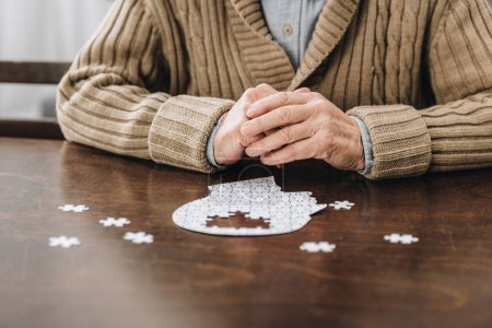 Photo for Cropped view of retired man playing with puzzles on table - Royalty Free Image