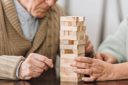 cropped view of retired couple playing jenga game at home