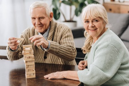 happy pensioners playing jenga game on table