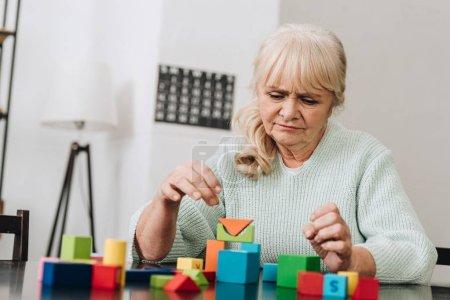 Foto de Mujer rubia jubilada jugando con juguetes de madera en casa - Imagen libre de derechos