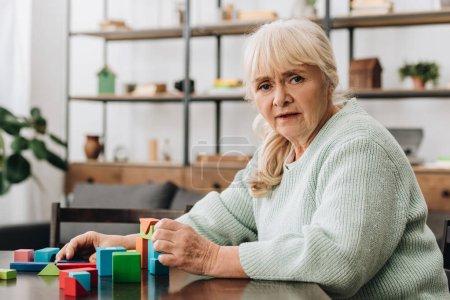 Photo pour Blonde senior femme assise près de jouets en bois à la maison - image libre de droit