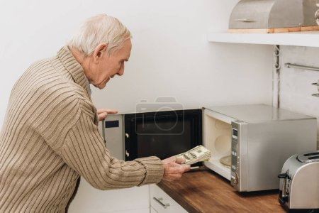 Photo for Senior man with dementia disease putting dollars in microwave oven - Royalty Free Image