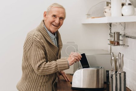 Photo for Happy senior man with dementia disease putting smartphone in toaster - Royalty Free Image