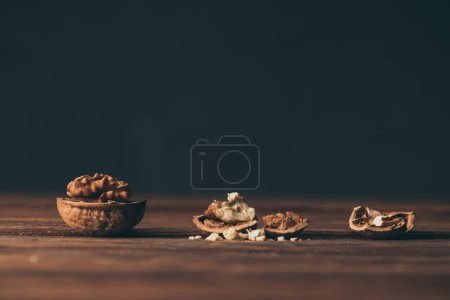 cracked walnuts as dementia symbol on wooden table on black background
