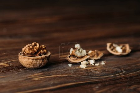 Photo for Walnuts in nut shells as dementia symbol on wooden table - Royalty Free Image