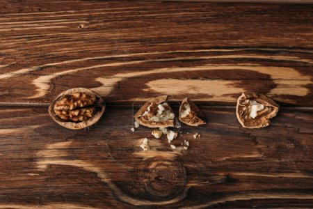 Photo for Top view of walnuts in nut shells as dementia symbol on wooden table - Royalty Free Image