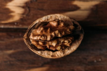 Photo for Top view of walnut in nut shell as dementia symbol on wooden table - Royalty Free Image