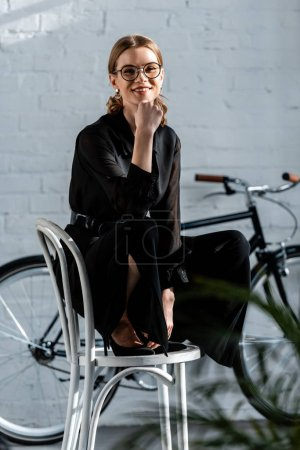 Photo for Attractive woman sitting on chair and smiling at camera - Royalty Free Image