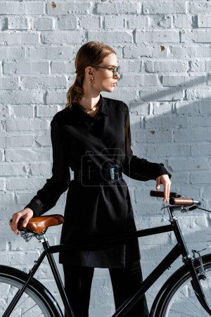 Photo pour Recadrée vue de jolie femme en vêtements noirs tenant vélo noir avec selle marron - image libre de droit