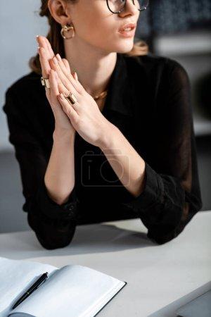 Photo pour Femme en noir vêtements et lunettes assis sur la chaise - image libre de droit