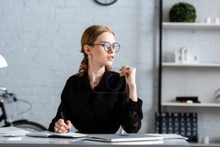 krásná obchodnice v černém oblečení a brýle sedí na židli a treska bezvousá v poznámce