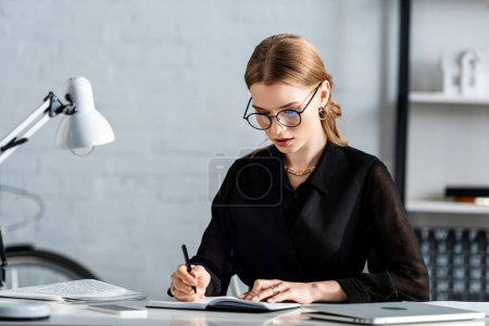 beautiful businesswoman in black clothes and glasses  writing and sitting on chair