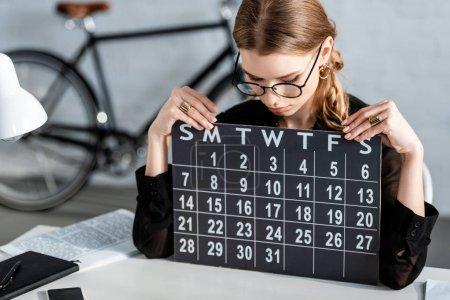 Photo pour Belle femme d'affaires en vêtements noirs et lunettes assis sur la chaise et en regardant le calendrier - image libre de droit