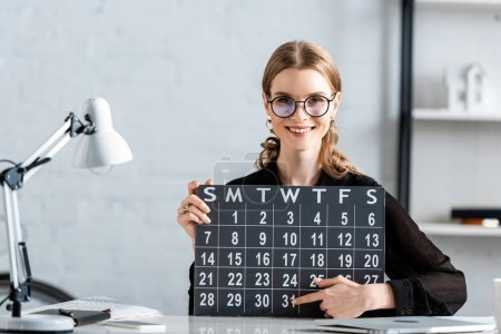 beautiful businesswoman in black clothes and glasses holding calendar and smiling at camera