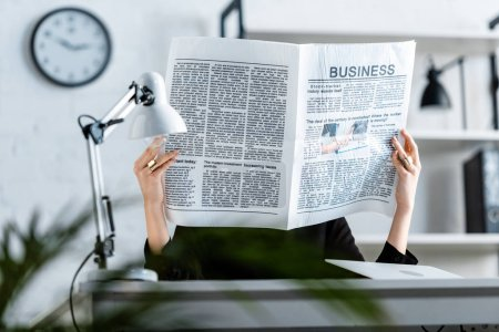 Photo for Businesswoman in black clothes sitting on chair while holding business newspaper in front of face - Royalty Free Image